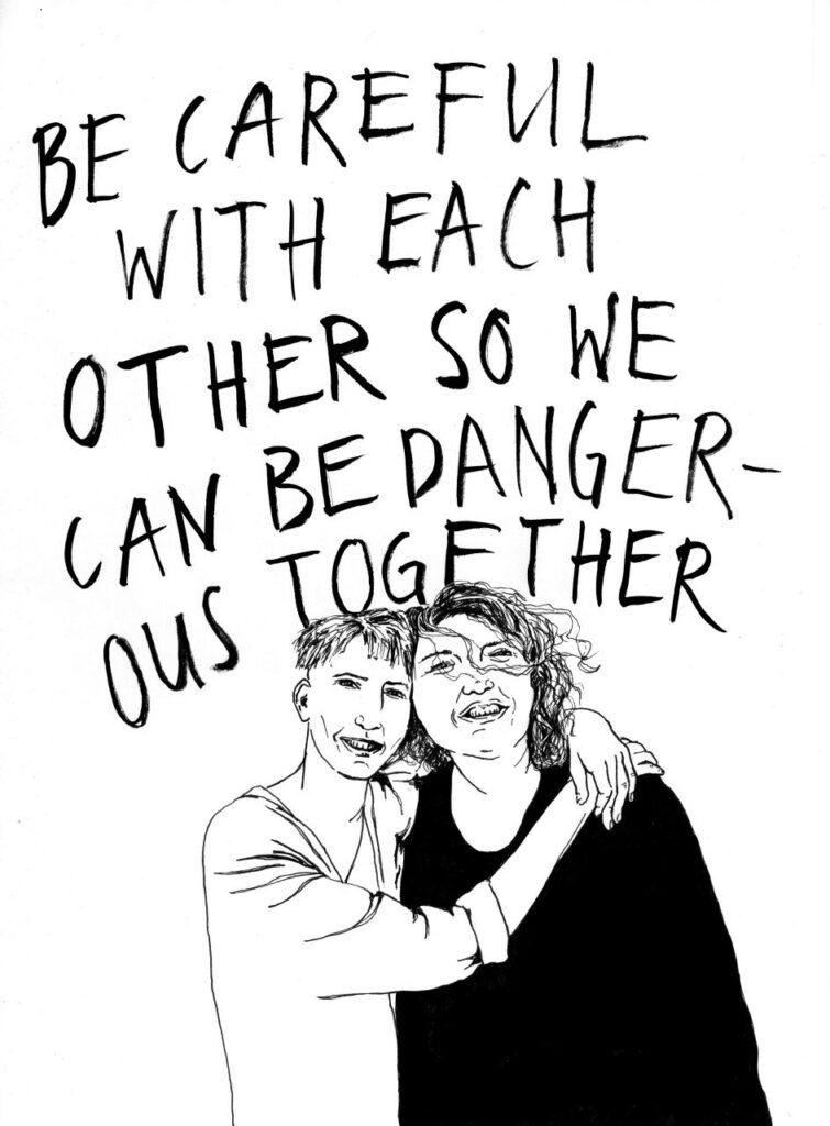 Be careful with each other so we can be dangerous together. Unter dem Schriftzug stehen zwei Menschen nahe beisammen und lachen.